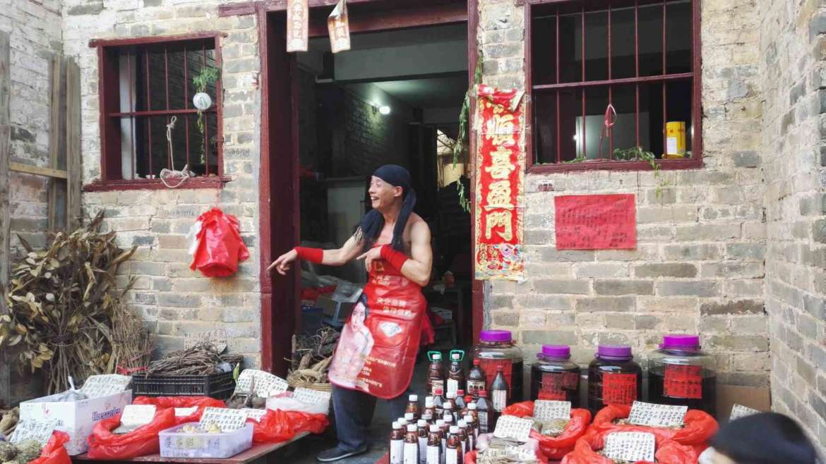 Guilin Karst Hills- A dancing seller in Huangyao Old Town